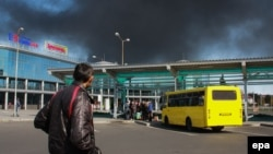 Ок атышуулардан улам күйүп жаткан Донецк аэрпортун карап турган киши. Донецк, 2-октябрь, 2014-жыл.