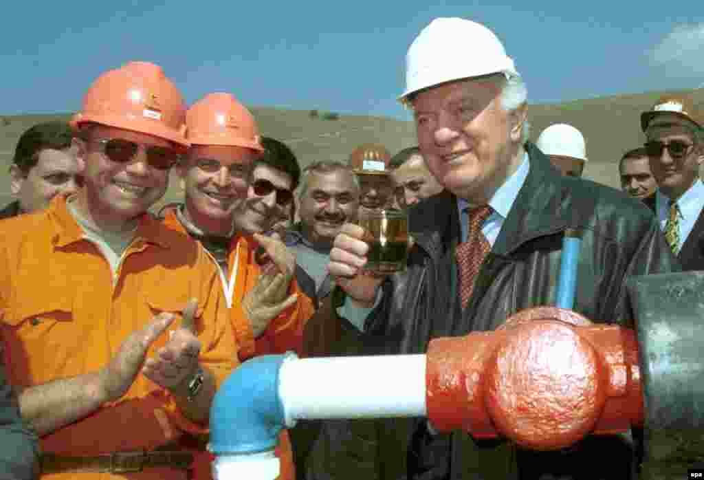 Georgian President Eduard Shevardnadze toasts with a glass of freshly extracted oil as he visits an oil field in Taribana near Tbilisi, during his 2000 election campaign.