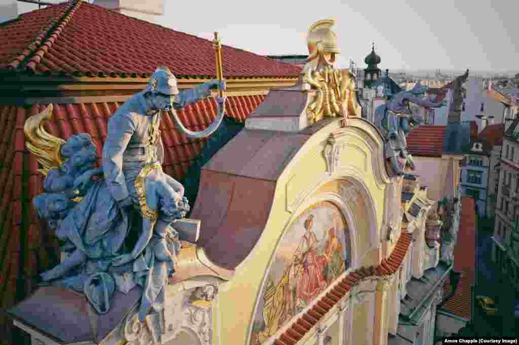 Një zjarrfikës që shpëton një grua nga flakët në çatinë e ndërtesës së vjetër të Kompanisë së Sigurimeve të Pragës, në Sheshin e Qytetit të Vjetër në Pragë. Skulptura dramatike është një nga veprat e fundit të përfunduara nga çeku Bohuslav Schnirch, para vdekjes së tij më 1901.