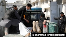 Men carry an injured person to the hospital after attacks mortar attacks in Kabul on March 7.