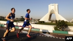 Runners in Iran's first international marathon pass Azadi Square in Tehran.