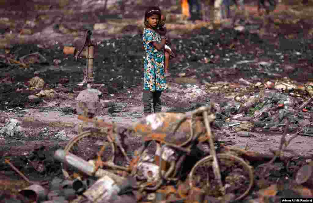 A girl carries her brother as she stands near her burnt home after a fire broke out in a slum area in New Delhi on April . (Reuters/Adnan Abidi)