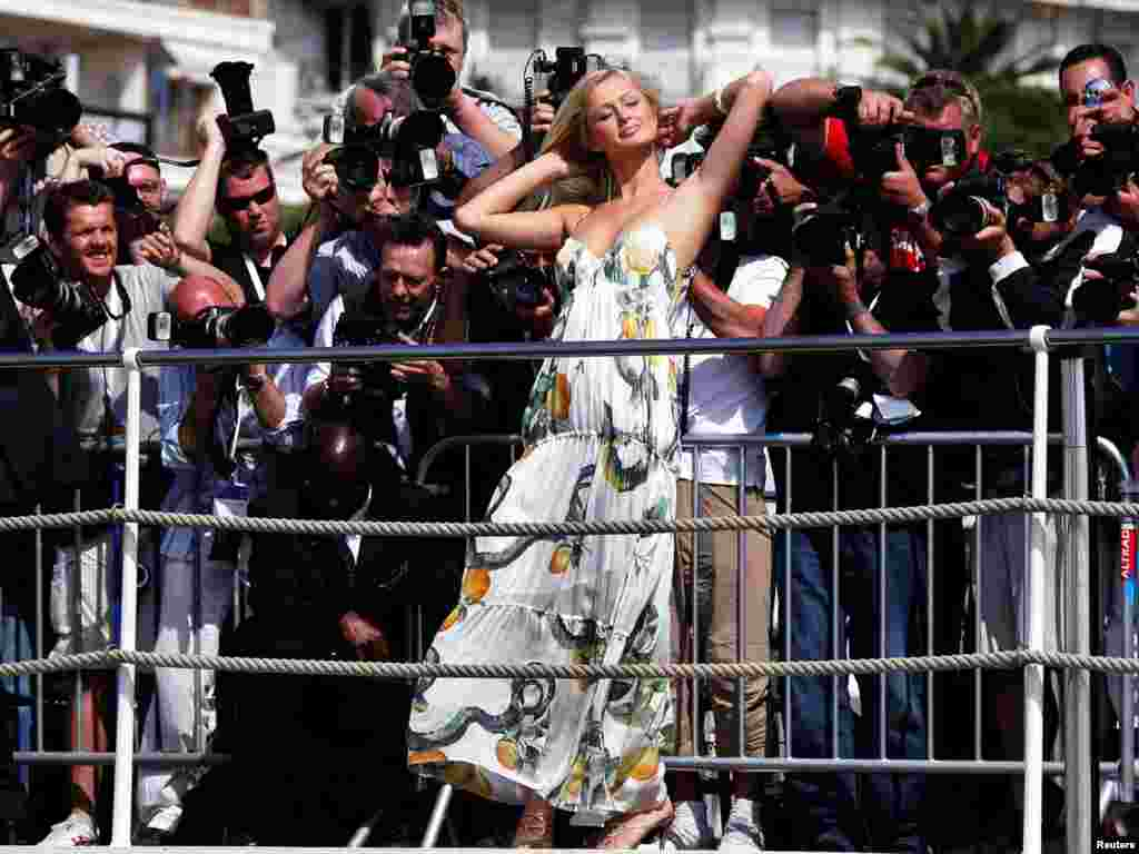 """U.S. hotels heiress Paris Hilton (C) poses at a photocall on the Carlton Hotel pier during the 58th Cannes Film Festival May 13, 2005. Hilton is visiting the festival to promote the film """"National Lampoon's Pledge This!"""", in which she stars. REUTERS/Eric Gaillard"""