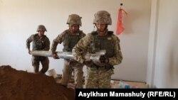 Солдаты выносят из разрушенного дома в Арыси снаряд. 29 июня 2019 года.