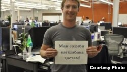 """Facebook founder and CEO Mark Zuckerberg with a sign in Tajik: """"I own this network."""""""