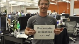 "Facebook founder and CEO Mark Zuckerberg with a sign in Tajik: ""I own this network."""