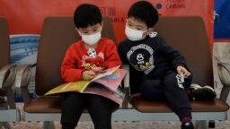 Copii purtând mască pentru a se păzi de coronavirus, într-o gară din Hong Kong