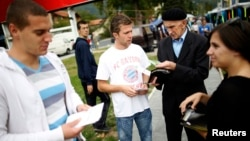 Volunteers hand out leaflets with information about new Bosnia's census in Jablanica, 60 kilometers south of Sarajevo, in September 2013.