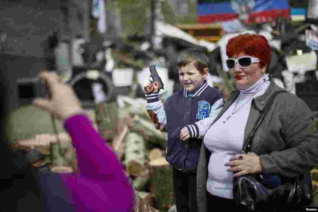 A boy with toy gun poses for picture in front of barricades at the police headquarters in the eastern town of Slovyansk, Ukraine, on April 17. (Reuters/Gleb Garanich)