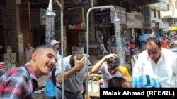Iraq - Men refresh themselves under shower in street, Baghdad, undated
