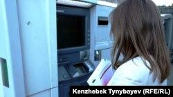 Банкоматтан ақша алып тұрған әйел. Алматы, 21 маусым 2013 жыл.