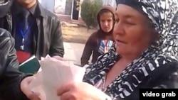 Скриншот видео, снятого Таджикской редакцией Азаттыка, на котором запечатлена женщина с несколькими бюллетенями в руках.