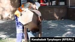 Дворник выгребает содержимое мусорной урны. Иллюстративное фото.