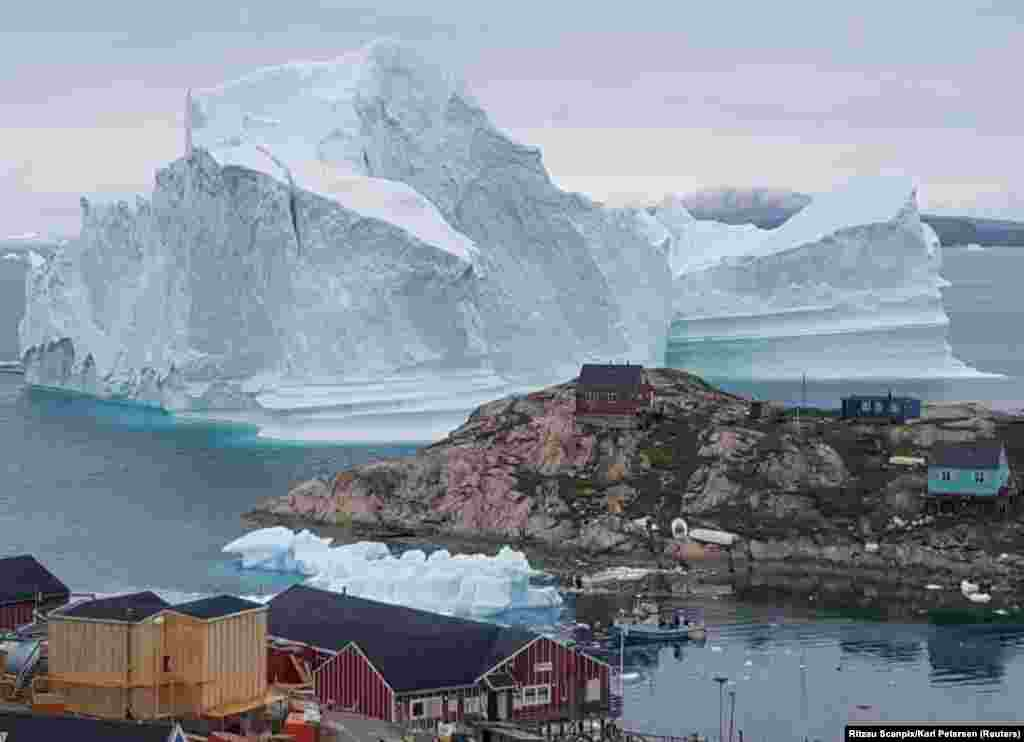 A giant iceberg is seen behind an Innaarsuit settlement in Greenland. (Reuters/Ritzau Scanpix/Karl Petersen)
