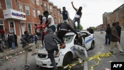 U.S. -- Demonstrators climb on a destroyed Baltimore Police car in the street near the corner of Pennsylvania and North avenues during violent protests following the funeral of Freddie Gray, April 27, 2015