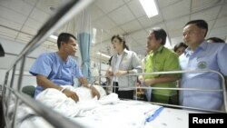 Kryeministri tajlandez, Yingluck Shinawatra, bisedon me njërin nga punëtorët e lënduar në uzinë.