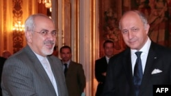 French Foreign Minister Laurent Fabius (right) welcomes his Iranian counterpart, Mohammad Javad Zarif, to the Foreign Ministry.