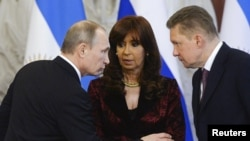 Russian President Vladimir Putin (left) with Argentinian President Cristina Fernandez (center) and Gazprom Chief Executive Officer Alexei Miller at a signing ceremony for energy deals in the Kremlin, Moscow, on April 23.