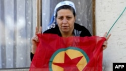 A Kurdish woman waves a PKK flag from her house in Diyarbakir, Turkey.