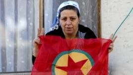 A Kurdish woman waves a PKK flag from her house in Diyarbakir, Turkey.