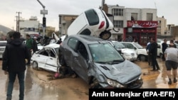 People stand near a pile of damaged cars after a flood hit the city of Shiraz on March 25.