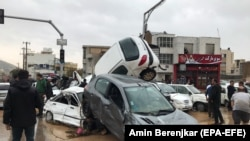 People stand near destroyed cars in the city of Shiraz on March 25.