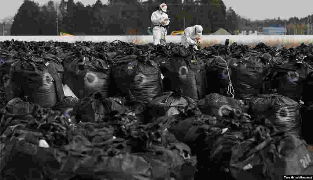 Працівники в захисних костюмах проводять збір радіоактивного ґрунту, листя й сміття в рамках знезараження території поблизу АЕС «Фукусіма-1», 24 лютого 2015 року