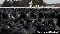 Disa punëtorë, të veshur me rroba mbrojtëse dhe maska, punojnë në dekontaminimin e qytetit Tomioka, që gjendet pranë centralit bërthamor në Fukushima. Foto nga arkivi.