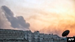 Smoke billows from the frontline district of Dahiyet al-Assad following an attack by rebels on Syrian regime forces in the northern city of Aleppo on October 29.