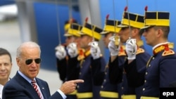 U.S. Vice President Joe Biden (light) inspects a guard of honor upon arriving