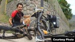 Cаяхатшы Мағжан Сағымбаев велосипедінің жанында отыр.