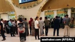 Люди в очереди у кассы в аэропорту Ашгабата.