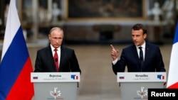 Володимир Путін (ліворуч) та Емманюель Макрон зустрінуться 25 травня в Росії
