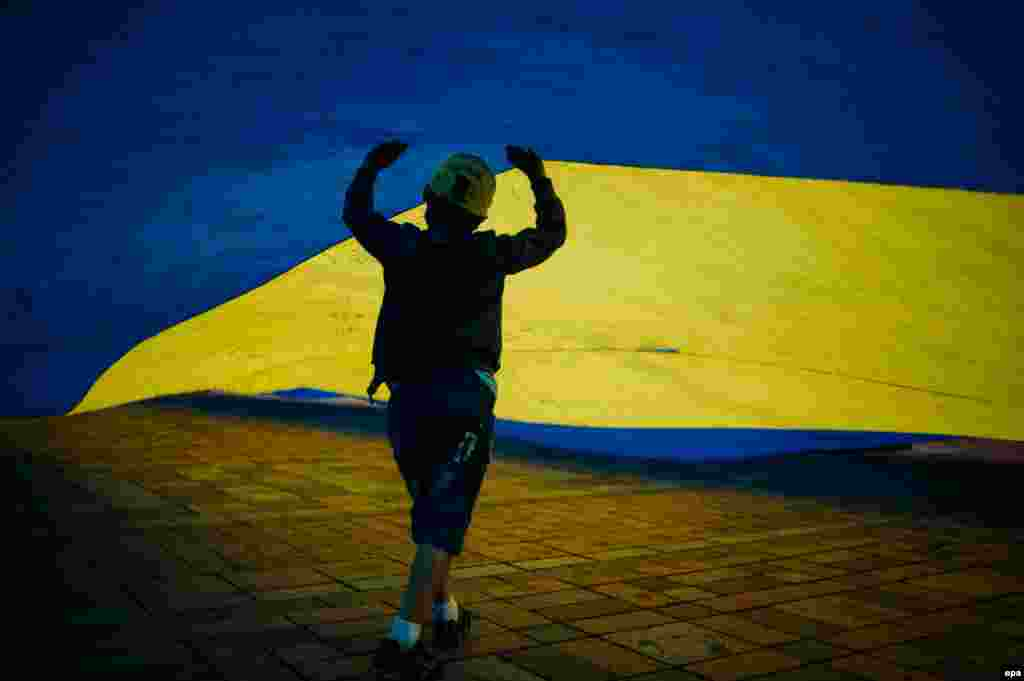 A child refugee plays under the Ukrainian flag during a rally on the sidewalk at the entrance to the parliament in Kyiv on June 5. (epa/Roman Pilipey)