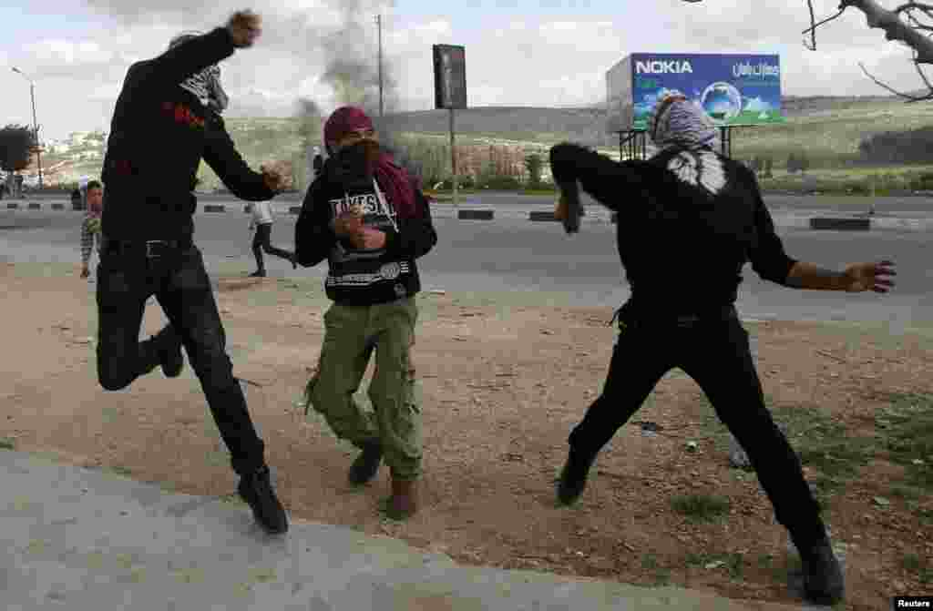 Palestinian protesters throw stones toward Israeli forces during clashes at Hawara checkpoint near the West Bank city of Nablus on March 1. (Reuters/Abed Omar Qusini)