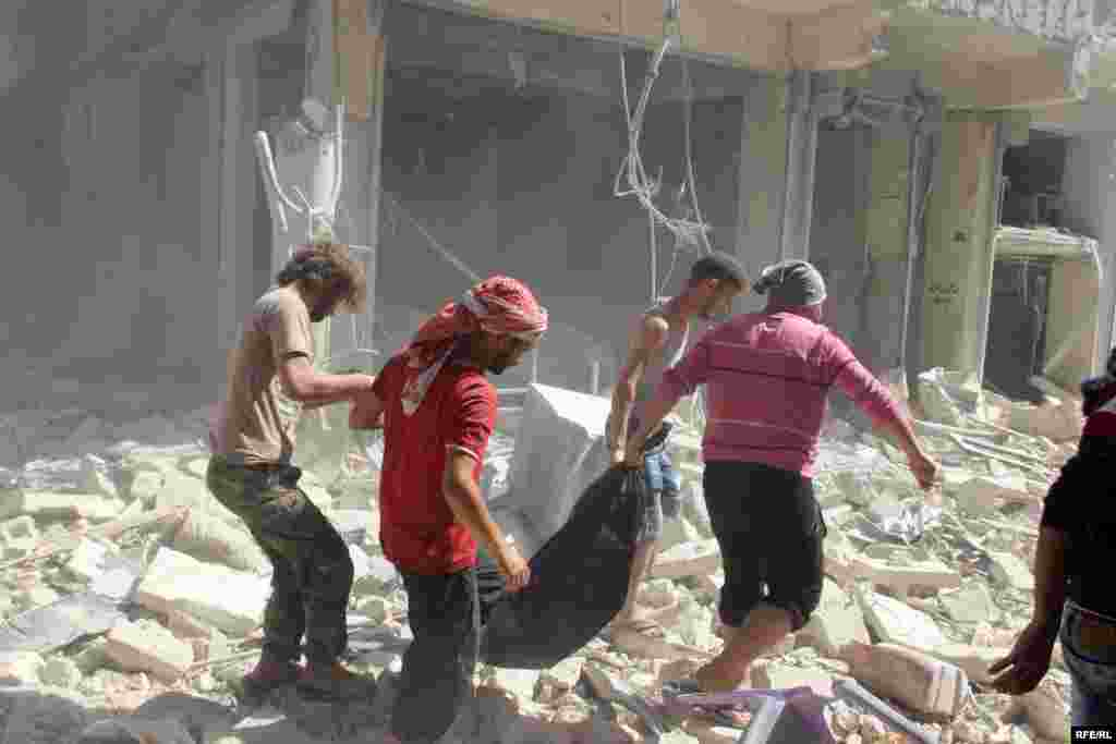 Civilians pull a body from the remains of a shattered building in Aleppo's Bustan al-Qasr district on October 11.