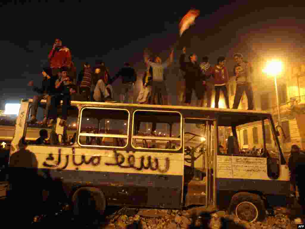 "Protesters celebrate on a wrecked bus used as a barricade with ""Let Mubarak Fall"" scrawled on it in Tahrir Square."