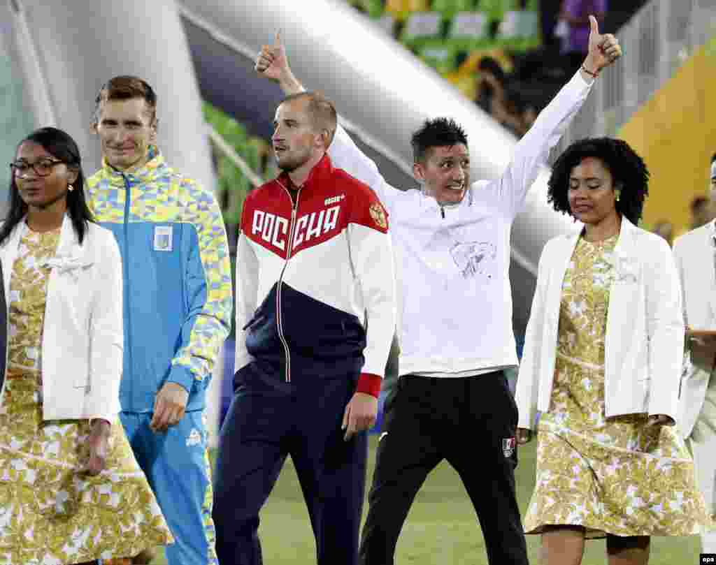 Gold medalist Aleksandr Lesun of Russia (center), silver medalist Pavlo Tymochenko of Ukraine (second from left), and bronze medalist Ismael Marcelo Hernandez Uscanga of Mexico stand during the awards ceremony in the men's modern pentathlon. Pentathlon involves fencing, swimming, riding, running, and shooting.