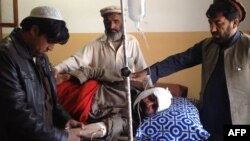 Relatives tend to an injured blast victim at a hospital in Kurram tribal district on January 30.