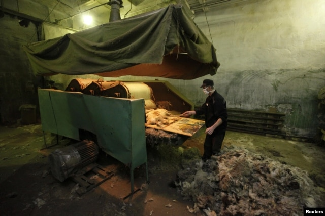"An inmate works at a Russian prison workshop manufacturing ""valenki,"" traditional knee-high sheep-wool-felt footwear, at a high-security men's prison in the Siberian city of Krasnoyarsk. (file photo)"