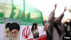 Iranian flag with portraits of Islamic Republic's founder, Ayatollah Ruhollah Khomeini (left), and his successor, Ali Khamenei, at a Tehran protest in mid-December.