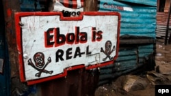 """Информационная табличка в трущобах Монровии, столицы Либерии. """"Эбола существует!"""""""
