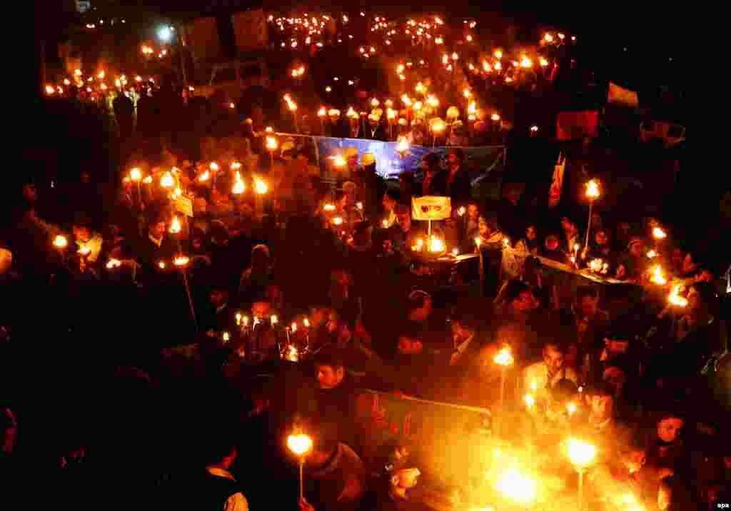 Жители пакистанского города Лахор зажгли факелы в первую годовщину нападения талибов на школу в Пешаваре, находящуюся под управлением вооруженных сил. 16 декабря 2014 года в результате теракта, который осуществили семеро боевиков, погибли 147 человек, большинство из них - дети.