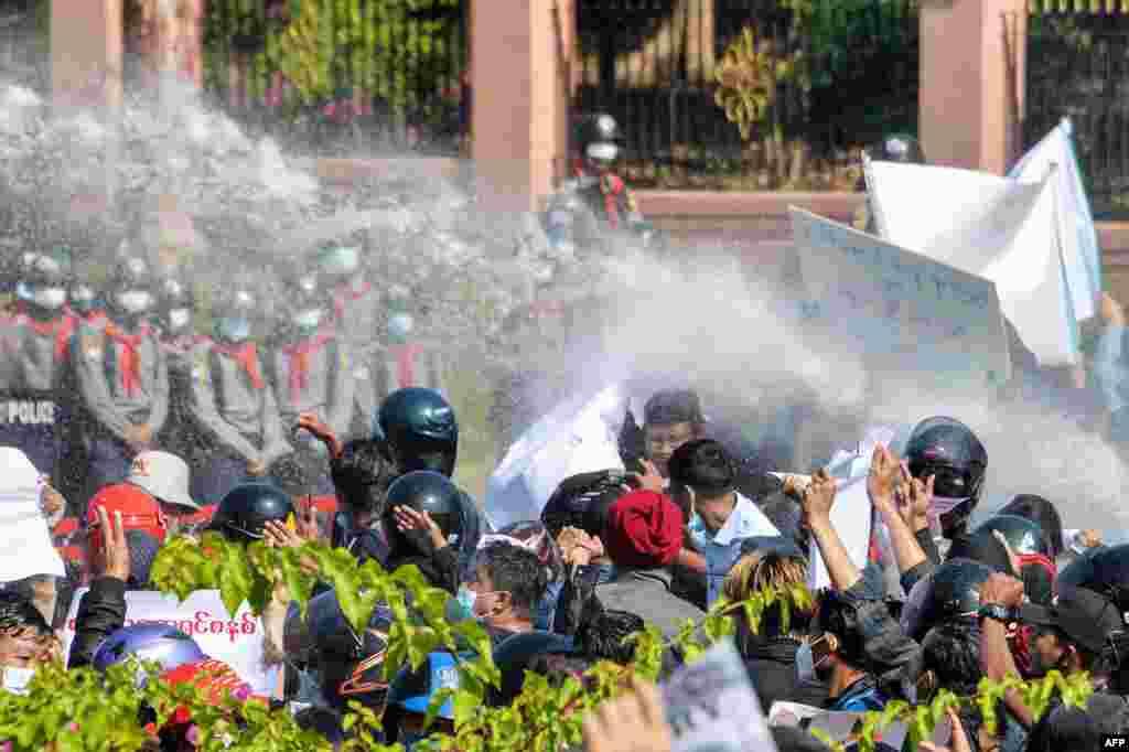 پولیس برما با استفاده از موترهای آبپاش در نایپیداو پایتخت این کشور در تلاش متفرق کردن معترضان است. این افراد در واکنش به کودتای نظامی که منجر به دستگیری آنگ سان سوچی رهبر این کشور شد اعتراض کرده و خواستار آزادی او شده اند. 9 فبروری 2021. عکس از:STR / AFP
