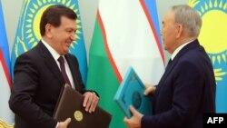 Өзбекстан президенті Шавкат Мирзияев (сол жақта) пен Қазақстан президенті Нұрсұлтан Назарбаев екі ел арасындағы құжаттарға қол қойған соң алмасып жатыр. Астана, 23 наурыз 2017 жыл.