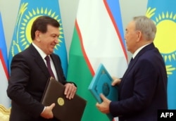 Kazakh President Nursultan Nazarbaev (right) and Shavkat Mirziyaev exchange documents during a signing ceremony following their meeting in Astana in March.
