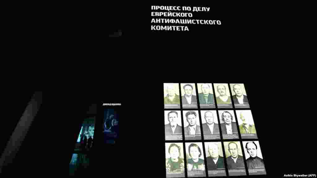 "Visitors walk in Jewish Museum in Moscow. The sign above the photos (right) reads: ""The Jewish Anti-Fascist Committee Trial."""