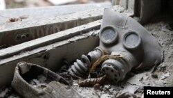 Жас баланың газтұтқысы мен аяқ киімі. Чернобыль атом электр станциясы маңындағы иен қалған Припять қаласы. 4 сәуір 2011 жыл.