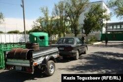 Баки для пищевых отходов, помещенные в тележку легковой машины. Город Ушарал Алматинской области, 9 июня 2012 года.