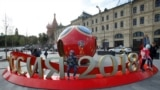 RUSSIA - People gather near decorations for the upcoming 2018 FIFA World Cup, with St. Basil's Cathedral seen in the background, in central Moscow, Russia June 7, 2018
